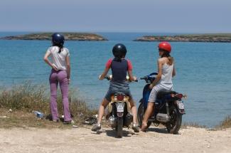 ITALIE - Pouille Jeunes filles en scooter devant la plage de Torre Guaceto, vers Brindisi
