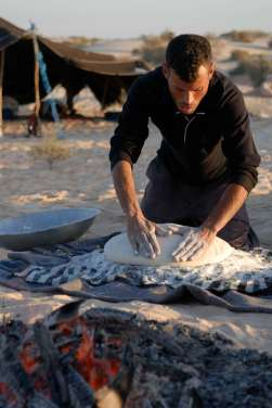 TUNISIE Désert à quelques km de Douz Ismaïl fait le pain, qu'il cuit sous la braise